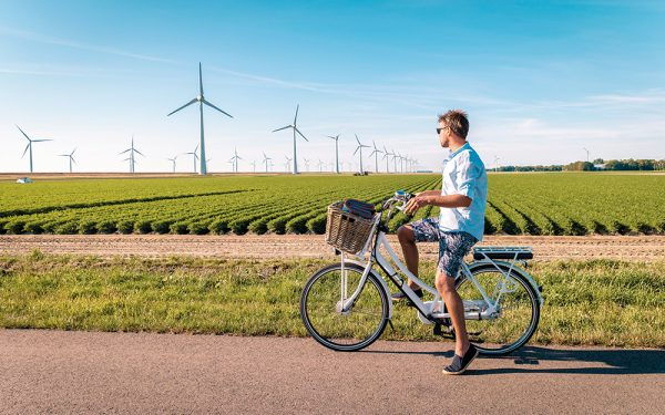 Young,Man,Electric,Green,Bike,Bicycle,By,Windmill,Farm,,